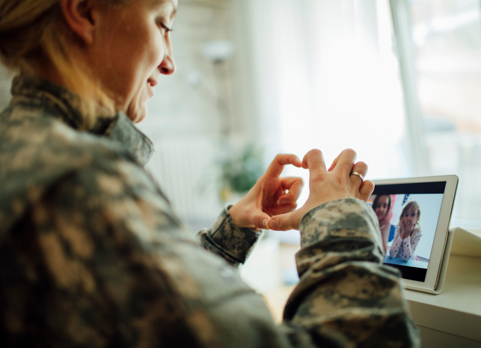 Military Mom talking with her children over digital tablet. Using modern technologies and communication to talk to her kids. Children making heart shape with fingers and mother touching screen. Shot with Canon EOS 5Ds